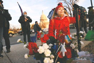 ?? MATT MCCLAIN/THE WASHINGTON POST ?? Melody Black cries as she kneels by a makeshift memorial for Ashli Babbitt outside the U.S. Capitol on Jan. 7. Babbitt, 35, was among pro-trump rioters at the Capitol on Jan. 6 when she was shot by a Capitol Police officer as she attempted to breach a set of doors deep inside the building.