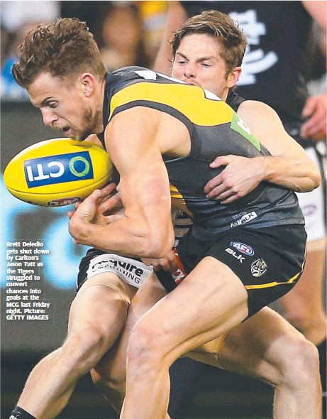 ?? Pic­ture: GETTY IM­AGES ?? Brett Dele­dio gets shut down by Carl­ton's Jason Tutt as the Tigers strug­gled to con­vert chances into goals at the MCG last Fri­day night.