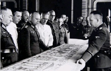 """??  ?? Herbert Jankuhn presents a section of the Bayeux Tapestry to German officers. His studies of the embroidery led him to the conclusion that it was a """"king's saga of purely Germanic imprint"""""""