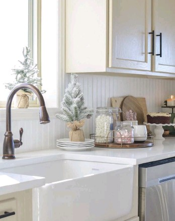 """??  ?? opposite: SARAH TAKES A MINIMAL APPROACH in her kitchen, choosing to dress up the décor she already has with subtle holiday touches. A mini faux tree on a tray brings holiday cheer to her kitchen island. """"I had it custom made from barn wood, and it's followed us from home to home all these years,"""" she says."""