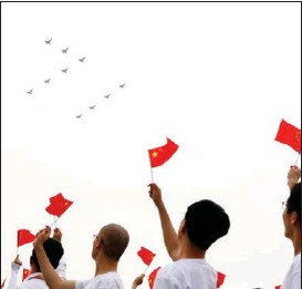 """?? ZHANG CHEN / XINHUA ?? People wave national flags while watching military aircraft fly overhead in a """"July 1"""" formation."""