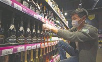 ?? (Tatyana Makeyeva/Reuters) ?? A SUPERMARKET employee arranges bottles of Russian sparkling wine on shelves in a shop in Moscow.