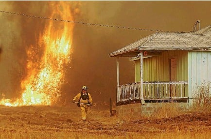 ?? PHOTO: REUTERS ?? A firefighter walks near a home as flames from the fast-moving Detwiler fire approach in Mariposa, California,