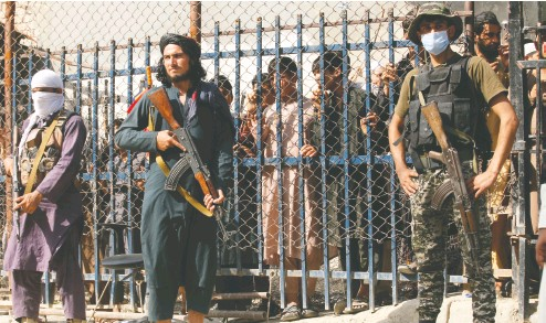 ?? MUHAMMAD SAJJAD / THE ASSOCIATED PRESS ?? Taliban fighters and a Pakistani paramilitary soldier stand guard on their respective sides at a border crossing point between Pakistan and Afghanistan earlier this week.