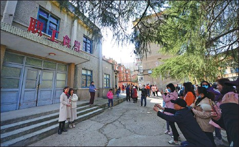 ?? XIE YONG / FOR CHINA DAILY Hi, Mom. The site ?? Film fans pose inside an old factory complex in Xiangyang, Hubei province, that was featured in the current blockbuster has quickly become a popular tourist attraction.
