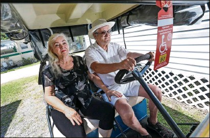 ?? Photos by IVY CEBALLO | Times ?? Wanda Boudreau, 71, and Larry Boudreau, 66, both with mobility issues, sit on their cart outside their mobile home in Hudson. Above, a sign warns no golf carts allowed beyond the intersection of Clark Street and Old Dixie Highway.
