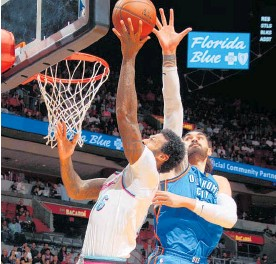 ?? Picture / Getty Images ?? Kiwi Steven Adams attempts to stop Miami Heat's James Johnson during Oklahoma City's resounding win yesterday.