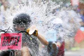 ?? IAN MAULE/Tulsa World ?? A racer is hit by a water balloon thrown by spectators during his race at Boulder Dash.