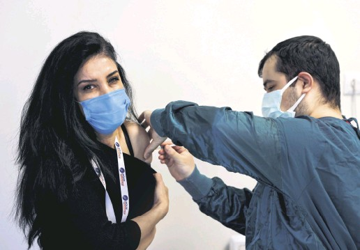 ??  ?? A woman receives a shot of the Pfizer-BioNTech vaccine at a hospital in Istanbul, Turkey, April 9, 2021.