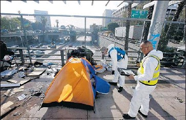 ?? Mark Boster Los Angeles Times ?? CITY CREWS clear out a tent belonging to a homeless person on Main Street above the 101 Freeway last month. A judge said homeless people were sometimes not allowed to retrieve medication and other key items.