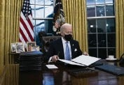 ?? EVAN VUCCI AP ?? President Joe Biden signs a series of executive orders Wednesday in the Oval Office.