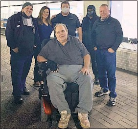 ?? PHOTO COURTESY OF JUSTIN DAVIS ?? Bruce Quinn of Grasonville tries out his new motorized wheelchair at Preston Automotive. Behind him, from left, are Justin Davis, founder of First Light for First Responders, Carrie O'connell, sales associate at Preston Ford, David Wilson Jr., president of Preston Automotive, another Preston employee who was in on the surprise and Jeff Risley, Quinn's best friend.