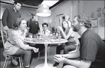 ?? By Jojo Whilden, HBO ?? Table talk: Judd Apatow works with creator/star Lena Dunham, left, and co-stars Alex Karpovsky, Chris Abbott and Allison Williams on a scene for Girls.