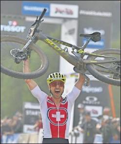??  ?? Nino Schurter levanta su bicicleta en meta para celebrar su triunfo.