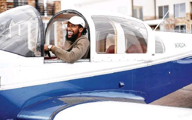 ?? Photos by Elizabeth Conley / Staff photographer ?? Texas Southern senior aviation student Fitzroy St. Jean laughs as he gets ready to take off at Ellington Airport in Houston.