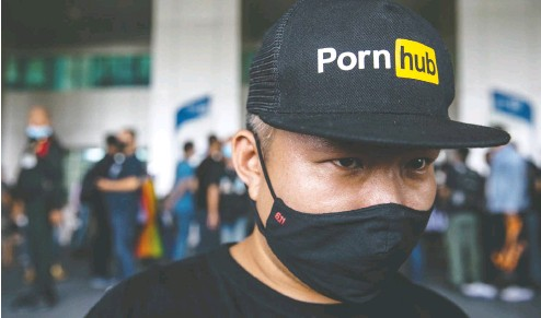 ?? LAUREN DECICCA / GETTY IMAGES FILES ?? A Thai protester wears a Pornhub hat at a rally outside the Ministry of Digital Economy and Society after the ministry banned the adult website in Thailand last November. Parent company MindGeek's fortunes tumbled the month after an expose was published in the New York Times.