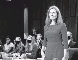 ?? ERIN SCHAFF/THE NEW YORK TIMES ?? Judge Amy Coney Barrett, with her family behind her, is sworn in to testify before the Senate Judiciary Committee on the first day of her Senate confirmation hearing.