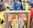 ??  ?? A royalist protester holds a framed picture of the late Thai king Bhumibol Adulyadej