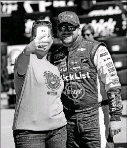 ?? John Raoux/The Associated Press ?? Prosper driver Chris Buescher takes a selfie with a fan in the garage area before practice for the NASCAR Daytona 500. Buescher, hoping to have success at Daytona for the first time, starts on the inside of the 11th row in Sunday's race.