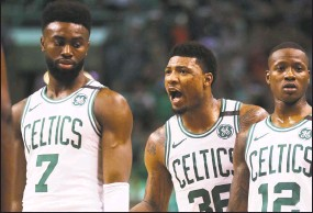 ?? Maddie Meyer / Getty Images ?? Marcus Smart, center, talks with teammates Jaylen Brown, left, and Terry Rozier during Game 5 of the Eastern Conference second round on Wednesday.