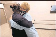 ?? ALEXA WELCH EDLUND/TIMES-DISPATCH ?? Office manager Susan Price hugs Saule Sadykova as she arrives at the Hanger Clinic.