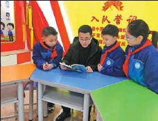 ?? PROVIDED TO CHINA DAILY ?? Ma Xun reads a book with students at Dongfeng Primary School in Zunyi and shares stories about his grandfather.