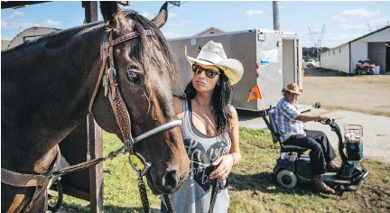 ??  ?? Annick Lepage from La Tuque pats her horse, Miss Rebel Fuel, after having a horseshoe replaced at the St-Tite Western Festival on Tuesday.
