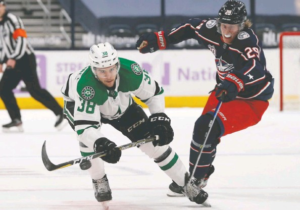 ?? JAY LAPRETE / THE ASSOCIATED PRESS ?? Dallas forward Joel L'Esperance chips the puck past Blue Jackets star Patrik Laine, who has already talked himself into the doghouse in Columbus.