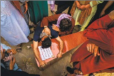 ?? Marcus Yam Los Angeles Times ?? A MAN weeps over the casket of Farzad Ahmadi, 12, one of seven children killed in an explosion in Kabul.