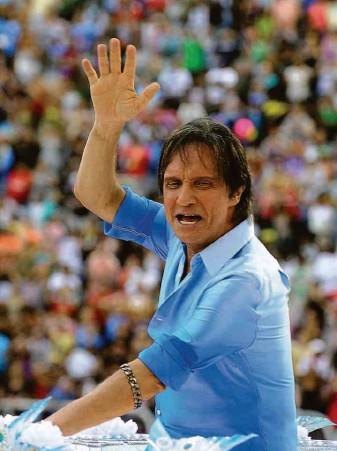 ?? Vanderlei Almeida - 8.mar.2011/afp ?? Roberto Carlos acena para o público da Sapucaí, no Rio, ao desfilar pela escola de samba Beija Flor, em 2011