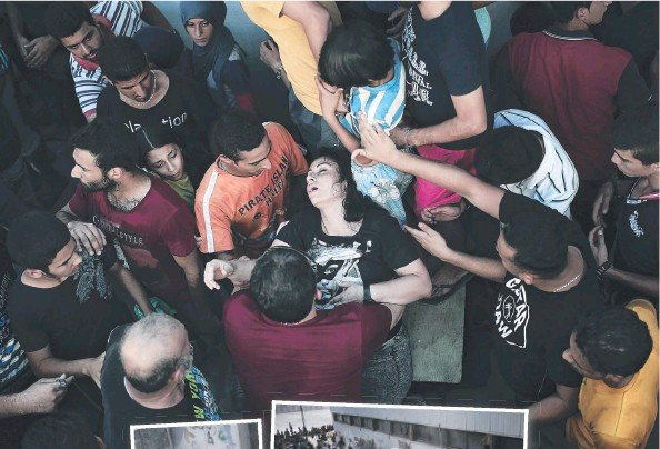 ??  ?? STAMPEDE: A woman faints during registration in Kos; and police use truncheons and fire extinguishers.