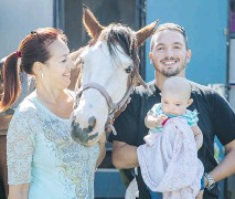 ??  ?? Charlene Frigon, left, Jacob Sheehy and their 4-month-old daughter KellyAnn have fun with Frigon's horse Sunshine outside their campsite at the St-Tite Western Festival on Wednesday.