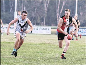 ?? PHOTO: Janet Watt ?? IN THE CONTEST: Myrtleford's Lochie Hourigan and Lavington's Connor Meredith give chase to the ball during the reserves match on Saturday.