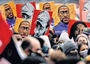 ?? REUTERS ?? People hold placards with paintings of George Floyd, Daunte Wright and Philando Castile — all killed at the hands of police officers — after the verdict in the trial of former Minneapolis police officer Derek Chauvin in front of Hennepin County Government Center, in Minneapolis, Minn. on Tuesday.