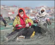 ?? WANG JIANMIN / XINHUA ?? Women prepare nets for the upcoming spring fishing season in Lianyungang, Jiangsu province, on Friday.