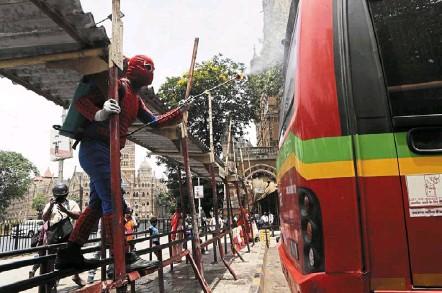 ?? — AP ?? Superhero sanitation: indian social worker ashok Kurmi wearing a spider-Man costume as he sanitises a public transport bus at a train station in Mumbai.