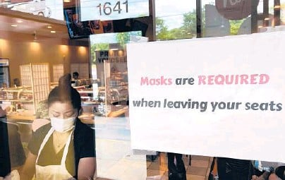 ?? NAM Y. HUH/AP ?? Small business owners throughout the country are dealing with changes due to a surge in COVID-19 cases as well as mask mandates in some places. Above, a sign notifying diners about mask protocol in June at a restaurant in Rolling Meadows, Illinois.