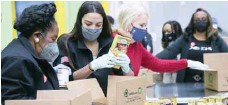?? — AFP ?? Congresswomen help distribute food at the Houston Food Bank on Sunday.