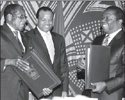 ?? Reuters photo: Philimon Bulawayo ?? DONE DEAL: Zimbabwe President Robert Mugabe, left, exchanges documents with opposition leader Morgan Tsvangirai, right, after signing a power-sharing deal at Rainbow Towers hotel in Harare on Monday.