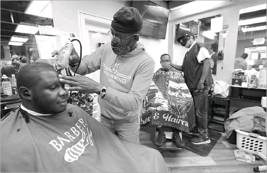 ?? Julio Cortez/the Associated Press ?? Kevin Fitzhugh (center left) cut Mabreco Wright's hair and Wallace Wilson (right) gave James Mcrae a trim on Friday in Hyattsville, Md. A team of barbers is working to provide factual information to customers about COVID vaccines.