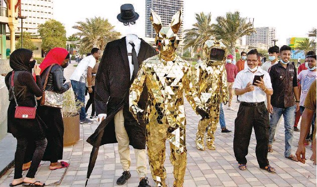 ?? Kamal Kassim / Gulf Today ?? ↑ The entertainers clad in mind-blowing outfits bring a lot of joy to the visitors of Al Majaz Park in Sharjah.