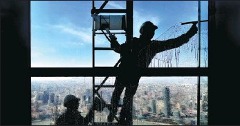 ?? YANG JIANZHENG / FOR CHINA DAILY ?? Workers clean a window at the Shanghai World Financial Center on Feb 9, just before Spring Festival.