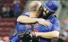 ?? JOHN MINCHILLO/ THE ASSOCIATED PRESS ?? Jake Arrieta hugs catcher David Ross after the final out of his no-hitter against the Reds on Thursday.