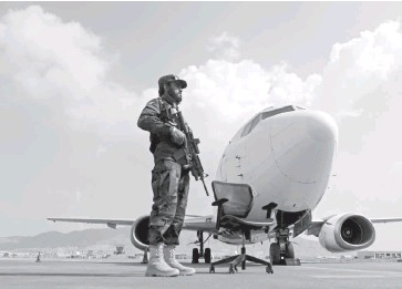?? KARIM SAHIB/AGENCE FRANCE-PRESSE/GETTY IMAGES ?? A Taliban fighter stands guard next to an Ariana Afghan Airlines aircraft at the Kabul airport on Sunday.