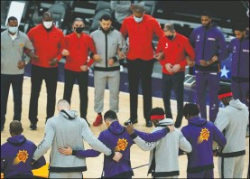 ?? AP PHOTO ROSS D. FRANKLIN ?? Members of the Phoenix Suns and the Toronto Raptors form a circle during the American national anthem prior to an NBA basketball game Wednesday in Phoenix.