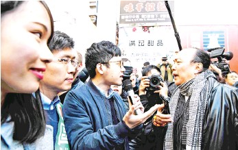 ??  ?? A man (right) shouts at disqualified pro-democracy lawmaker Nathan Law (centre) as Au (second left) and Chow (left) look on as they gather to campaign on behalf of Au for the Legislative Council by-elections in Hong Kong. — AFP photo