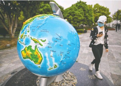 ?? HECTOR RETAMAL/AFP VIA GETTY IMAGES ?? A woman wearing a face mask looks at a globe in a park in Wuhan in China's central Hubei province as thousands of Chinese travellers rushed to leave the coronavirus-ravaged city after authorities lifted a ban on travel.