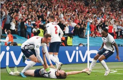 ?? Foto Laurence Griffiths/AFP ?? Harry Kane (na tleh) je z zmagovitim golom v podaljšku tekme z Dansko spravil v delirij rojake v 55-milijonski Angliji.
