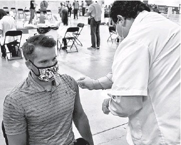 ?? STEVE METSCH/NAPERVILLE SUN ?? Joe Castellano, a Jewel-Osco pharmacist based in Naperville, swabs the arm of Tim O'Connor during a mass event at the former Sam's Club store in Naperville.