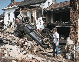 ?? VALENTIN BIANCHI / AP ?? A woman on Monday takes in the devastation left by the flooding in Liege, Belgium. The country held a day of mourning on Tuesday for the victims of the disaster.